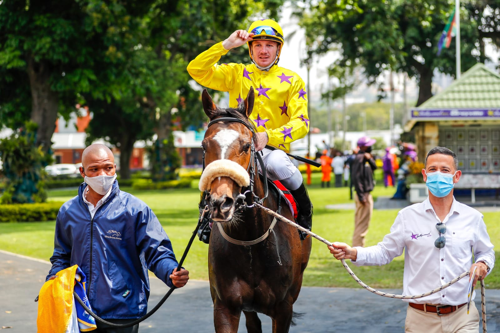 Horse IMBEJEJE being led in after winning at Hollywoodbets Greyville. Jockey saluting.